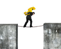 Businessman carrying golden dollar sign balancing on rusty chain Royalty Free Stock Photo