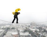 Businessman carrying golden dollar sign balancing on tightrope Stock Photos