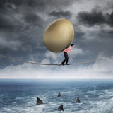 Businessman carrying golden egg above sea Royalty Free Stock Image