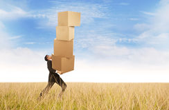 Businessman carrying heavy boxes outdoor. Businessman is carrying plenty of boxes at the field under blue sky Stock Images