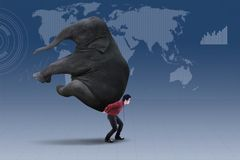 Businessman carrying heavy elephant over world map Stock Photography