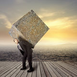 Businessman carrying heavy stone package. Businessman carrying heavy package - concept of tough career in the business Royalty Free Stock Photography