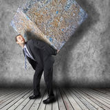 Businessman carrying heavy stone package Stock Photo