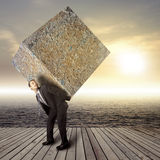Businessman carrying heavy stone package. Businessman carrying heavy package - concept of tough career in the business Royalty Free Stock Image