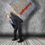 Businessman carrying heavy stone package Stock Photos