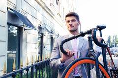 Businessman carrying his bicycle Royalty Free Stock Photo