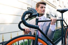 Businessman carrying his bicycle Stock Images