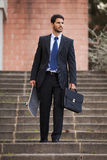 Businessman carrying his skateboard Royalty Free Stock Image