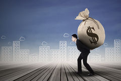 Businessman carrying a money sack Stock Photo