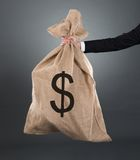 Businessman carrying moneybag with dollar sign Royalty Free Stock Image