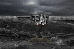 Businessman carrying old structure of FEAR on rock in dark ocean Stock Photo