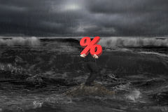 Businessman carrying percentage 3D symbol on rock in dark ocean Stock Photos
