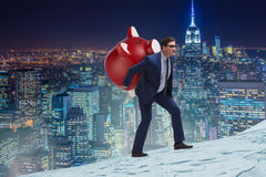 The businessman carrying the piggybank with savings Stock Photography
