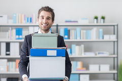 Businessman carrying a pile of boxes and folders Stock Photo