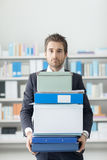 Businessman carrying a pile of boxes and folders Stock Photos