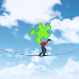 Businessman carrying puzzle on the rope Stock Photo