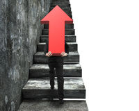 Businessman carrying red arrow sign climbing on stairs Royalty Free Stock Image