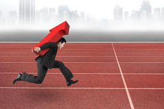 Businessman carrying red arrow up running on track Stock Photos
