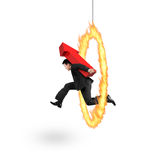 Businessman carrying red arrow up sign jumping through fire hoop Stock Photography