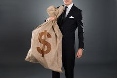 Businessman carrying sack with dollar sign. Midsection of businessman carrying sack with dollar sign against gray background Royalty Free Stock Photography