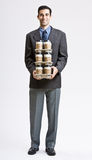 Businessman carrying stack of coffee cups Royalty Free Stock Photography