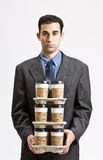 Businessman carrying stack of coffee cups Royalty Free Stock Image