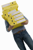 Businessman carrying stack of yellow folders, low angle view, cut out Royalty Free Stock Image