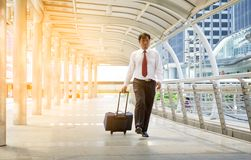 Businessman carrying a suitcase on passage of modern building Royalty Free Stock Photo