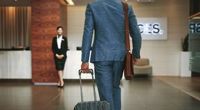 Business traveler arriving at hotel. Businessman carrying suitcase while walking in hotel lobby. Business traveler arriving at hotel with female receptionist Royalty Free Stock Photos