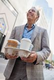 Businessman carrying takeaway cups Royalty Free Stock Photos