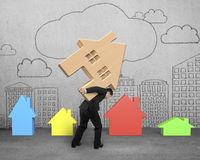 Businessman carrying wooden house on his back Stock Photography