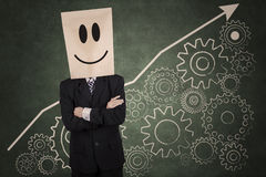 Businessman with carton head and gear Stock Photography