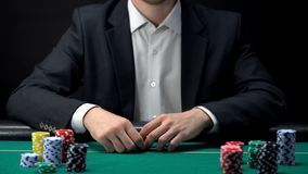 Businessman at casino ready for start of new poker game, gambling addiction stock photo