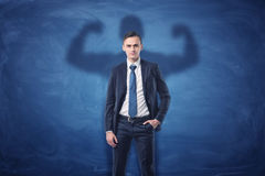 Businessman is casting shadow of big strong muscular man showing his biceps. On blue chalkboard background. Inner strength. Leadership qualities. Business royalty free stock image
