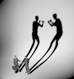 Businessman casting shadow of two fighters Royalty Free Stock Photos