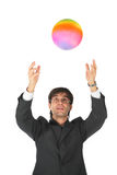 Businessman catches multicolor ball Stock Photography