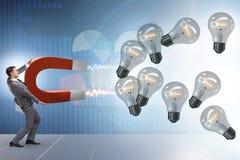 The businessman catching light bulbs on horseshoe magnet Stock Photo