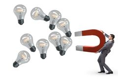 The businessman catching light bulbs on horseshoe magnet Royalty Free Stock Photography