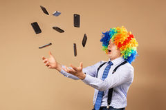 Businessman catching mobile phones falling from above. Close-up Portrait of business man in clown wig. Business concept Stock Image