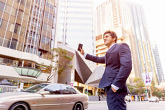 Businessman Catching Taxi In City Royalty Free Stock Photos