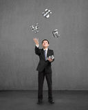 Businessman catching and throwing 3D sliver money symbols. Businessman throwing and catching 3D sliver money symbols with concrete background Royalty Free Stock Photography