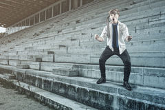 Businessman celebrate. Businessman watching the game alone on stadium and celebrate the goal royalty free stock photo