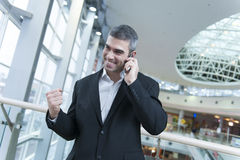 Businessman celebrates talking on mobile phone Royalty Free Stock Photos