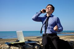 Businessman celebrating deal on the phone in front of the ocean Royalty Free Stock Image