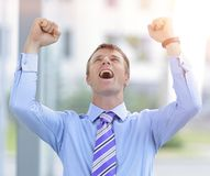 Businessman celebrating with his fists raised in the air. Celebrating success. Excited young businessman arms up, standing in office with city in background Stock Photography