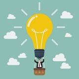 Businessman celebrating in lightbulb balloon Stock Images