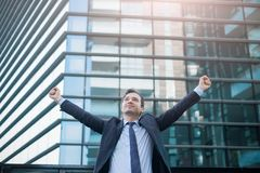 Businessman celebrating rising his arms after good news. Portrait of one manager after contract agreement stock photo