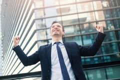 Businessman celebrating rising his arms after good news. Portrait of one manager after contract agreement stock images