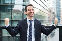 Businessman celebrating rising his arms after good news. Portrait of one manager after contract agreement stock photography