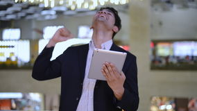 Businessman celebration his success while looking at a digital tablet stock video